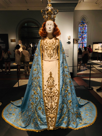 Mannequin dressed as Virgin Mary in satin brocade gown and ornate crown.
